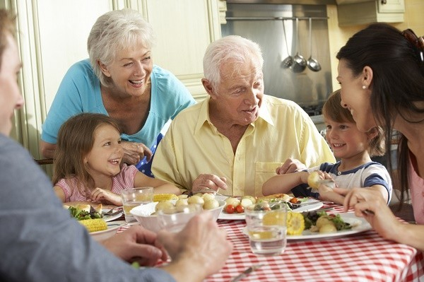 Multi Generation Family Eating Meal Together In Kitchen