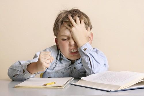 Những căng thẳng, áp lực ở trường học có thể là nguyên nhân dẫn tới đau đầu căng cơ ở trẻ em.