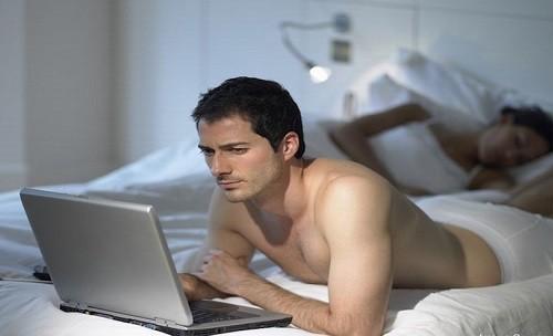 Man using laptop as wife sleeps