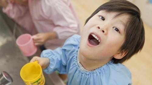 Giúp con nhẹ nhàng súc miệng bằng nước muối ấm.