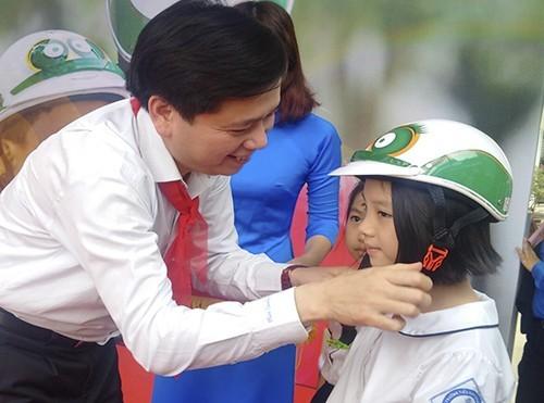 Đồng chí Nguyễn Long Hải - Bí thư Trung ương Đoàn, Chủ tịch Hội đồng Đội Trung ương tặng mũ bảo hiểm cho các em học sinh tại chương trình