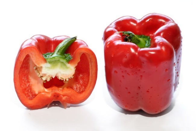 """Bell pepper A whole and cross-section of a red bell pepper (pepper in the UK and capsicum elsewhere in the Commonwealth). This cultivar of Capsicum annuum has a recessive gene that eliminates the capsaicin in the fruit. The pepper scores zero on the Scoville scale, meaning it has none of the """"heat"""" that other chili peppers do."""