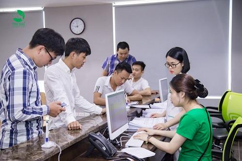 Nhân viên quầy lễ tân hướng dẫn người bệnh điền thông tin vào hồ sơ khám bệnh